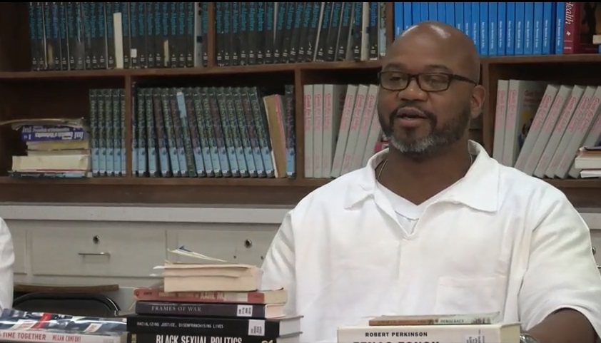Middle-aged black man in glasses behind a desk covered in books, with a background of many books